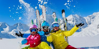 Three skiers posing in front of their skis sticking up in the snow and in front of snowy mountains