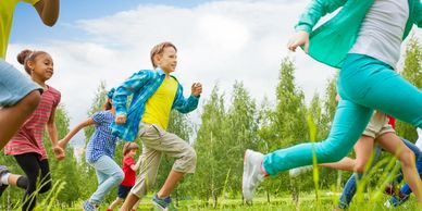 Children running through a grassy field with trees in the bckground