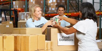 Group of volunteers at a food bank boxing up donations.