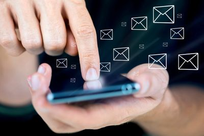 Finger tapping smartphone with e-mail envelope images floating above