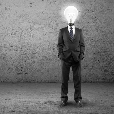 Man wearing a suit with a bright light bulb for a head, with a great idea for a Jingle.