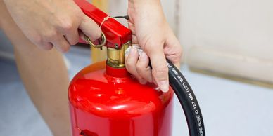 Fire Marshall trainee demonstrating how to remove the pin on a Fire Extinguisher