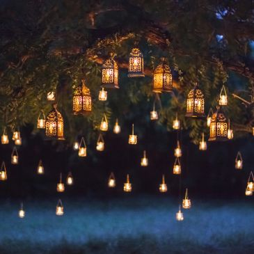 Outdoor event decor with lanterns suspended from tree