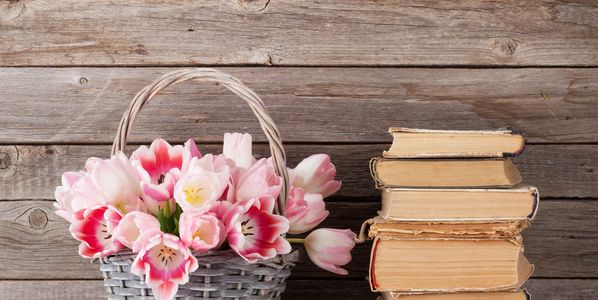 A basket of flowers and a pile of books.