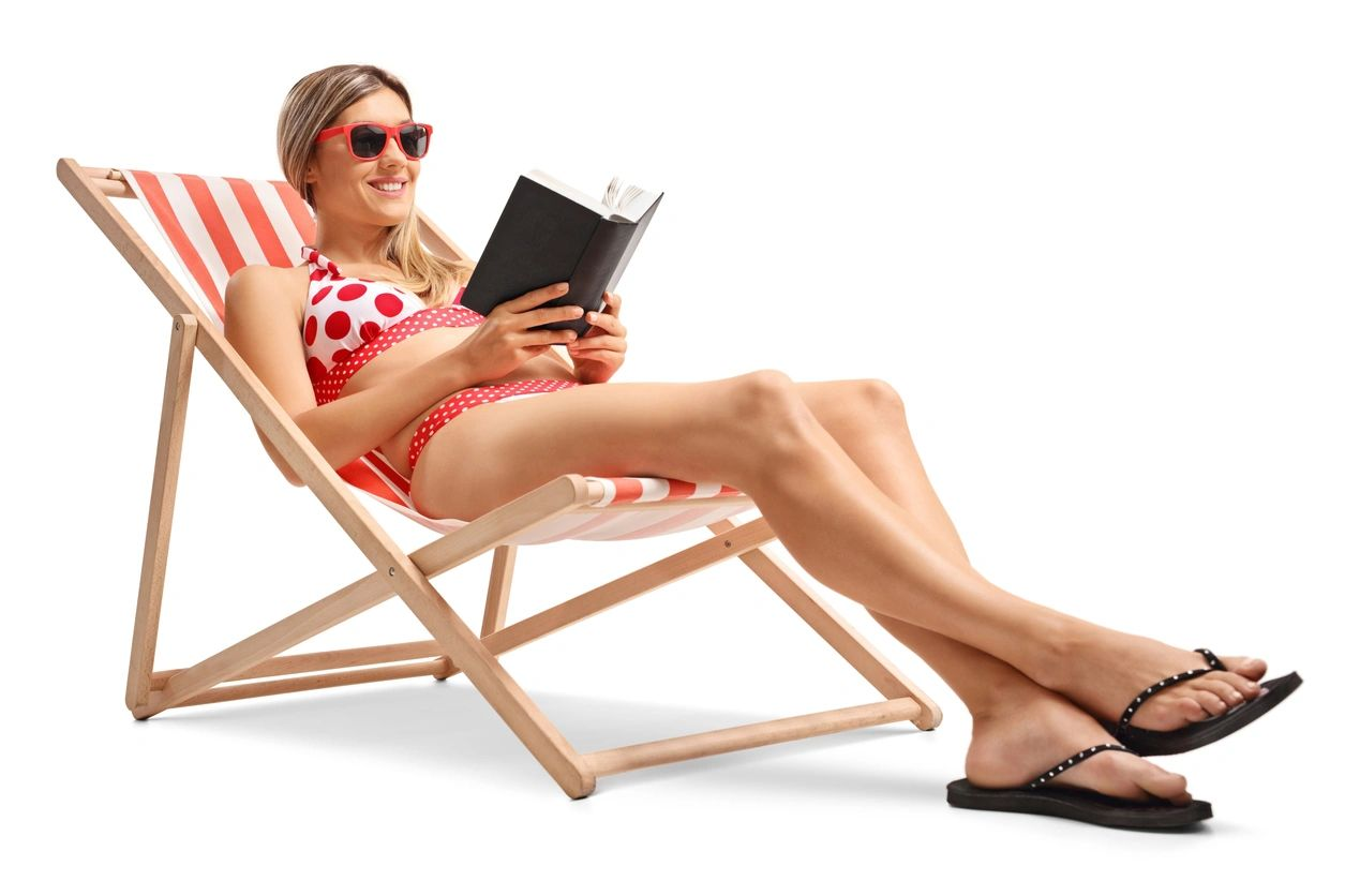 Woman in swimsuit on deckchair reading and smiling