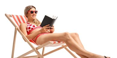 Woman on deckchair in swimsuit reading and smiling