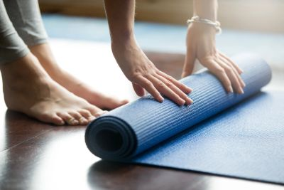 Woman rolling up yoga mat, just hands and feet showing.