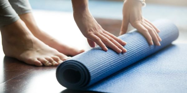 woman unrolling yoga mat