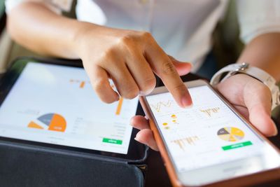 Business reports, graphs, and pie charts on handheld devices
