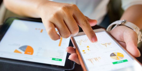 A Human with a tablet and smartphones where the gadget's screen are sharing the same display of a page full of charts and graphs of analytics.