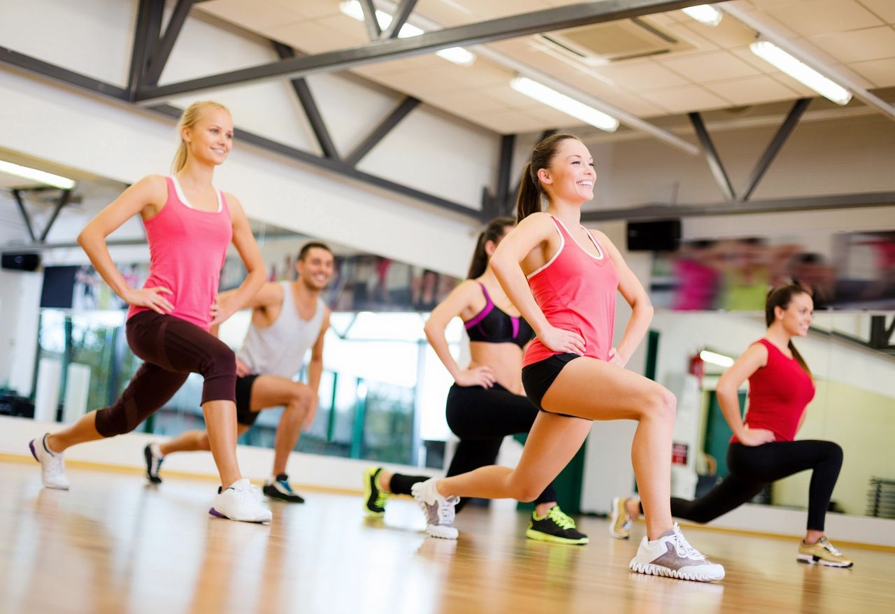 A group exercise class lunging and smiling.