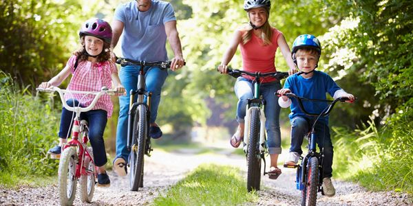 Family riding bikes and wearing helmets