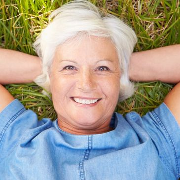 Middle Aged Woman with Broad Smile Reclining in Grass, Advertising Individual Dental Insurance