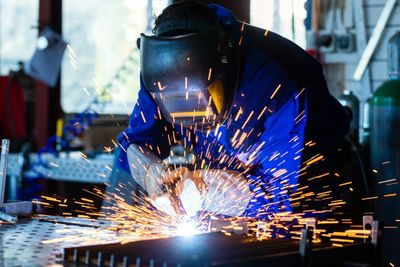 welder wearing protective equipment welding with sparks flying