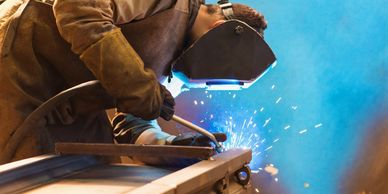 A professional coded welder welds a metal structur on site, wearing welding gloves and welding mask