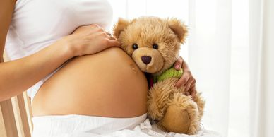 A woman full term pregnant holding a teddy in one hand and her belly with the other hand