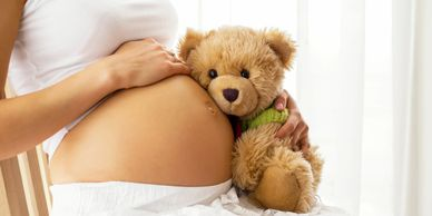 Pregnant mom with a teddy bear next to her stomach