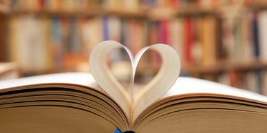 Open book with pages curled in to the spine to create a heart shape