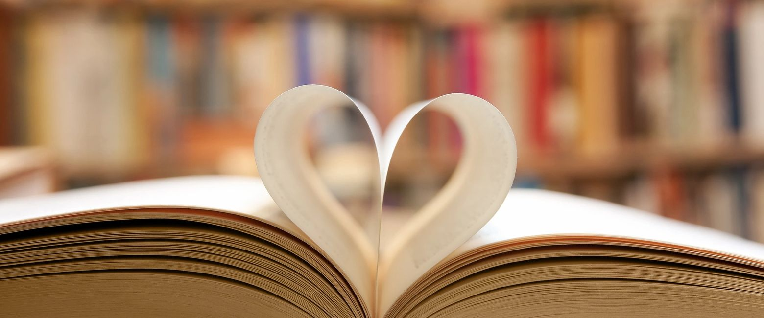 A book opening with a heart image placed centrally.