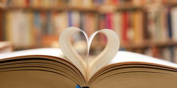 An image of an open book with a page shaped into a heart