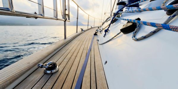 Image of yacht deck, railings and ropes at sea.