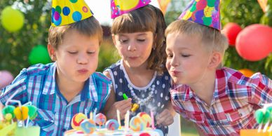 girls and boys at a birthday party with balloons and hats blow out candles on a cake
