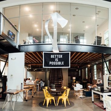"Contemporary office space with groups of workers collaborating and a sign overhead that reads, ""Better is Possible."""
