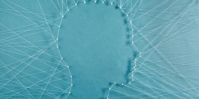 Graphic art forming a human head silhouette form white treads on a blue background.
