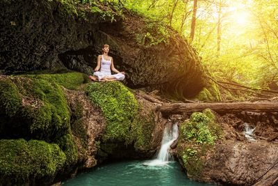 White presenting woman sitting on a moss covered rock in a very green forest in front of a natural pool of water from a creek.
