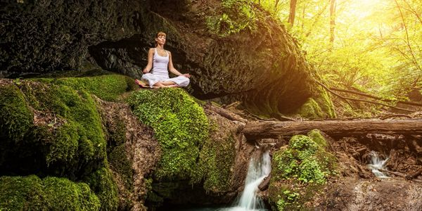 A women sitting out in nature in a meditative pose, with a waterfall is streaming below her