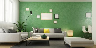 Green living room wall with a few picture frames hung on the wall
