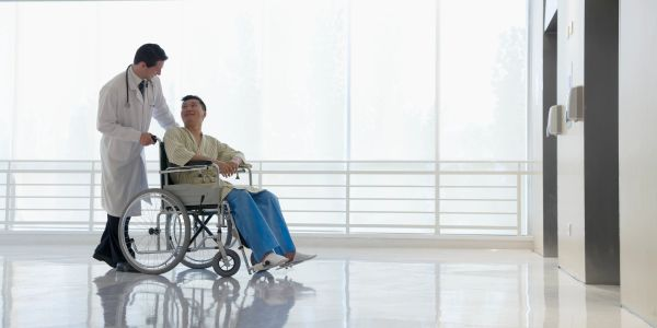 a man who has a catastrophic injury is sitting in a wheel chair looking at his doctor