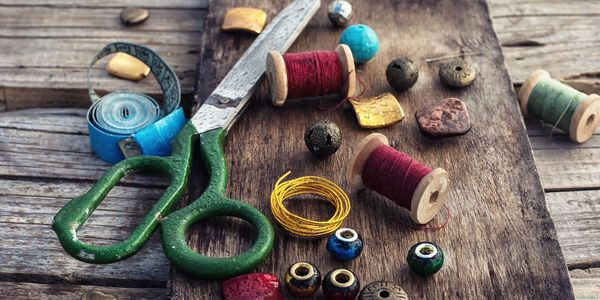 A picture of colorful jewelry making items, thread, beads and scissors.