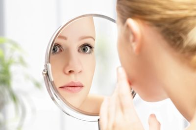 Woman looking in mirror at her acne