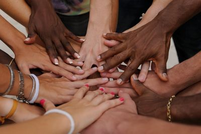 Hands of different skin tones and melanin shades all reach together and touch.