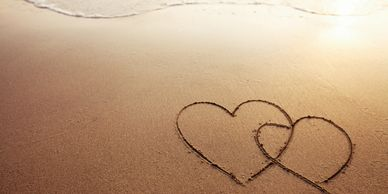 Two hearts drawn in the sand on the beach.