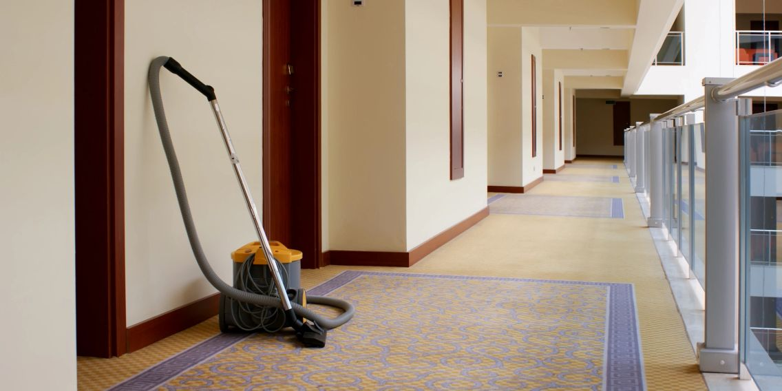 A long hallway with a commercial vacuum leaning against the wall.