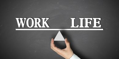 "A hand holding a triangle with the words ""Work"" and ""Life"" to show that they are balanced."