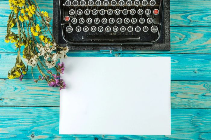 Image of a typewriter on a desk with writing paper