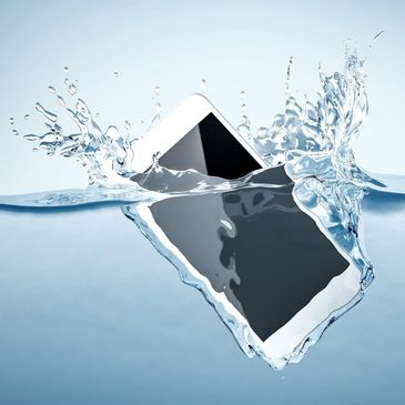 An iPhone has dropped into liquid. Splashes of water as the apple iPhone is submerged in water.