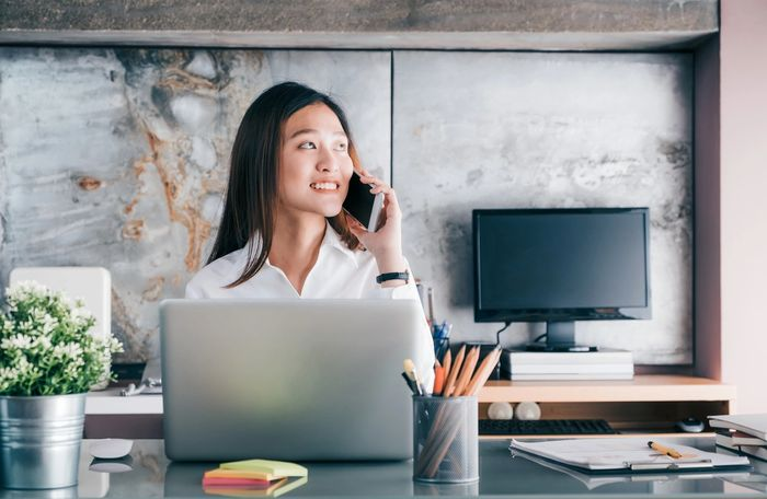 Asian woman smiling while holding a cell phone to her left ear. Sitting at her desk.