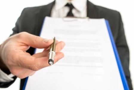 A person holding up an application in one hand and offering a pen with the other hand.