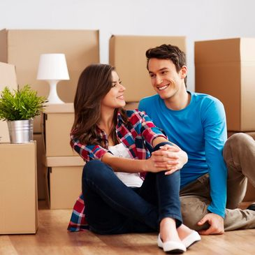 Happy young couple sitting on living room floor surrounded by boxes.