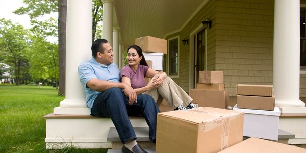 Couple happily sitting outside a house that are about to move in