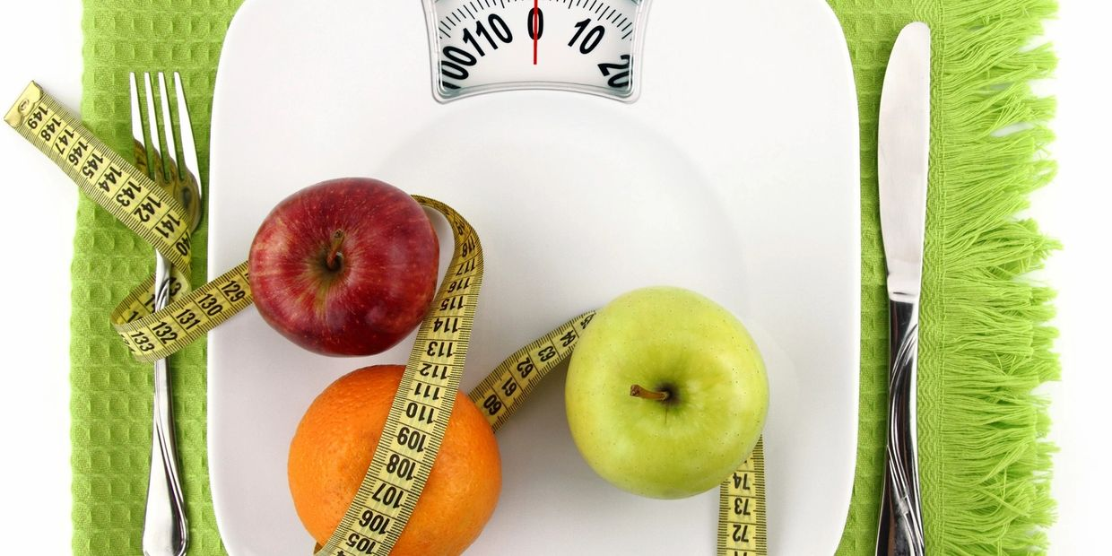 A place setting with a scale as a plate, with apples, orange and tape measure.