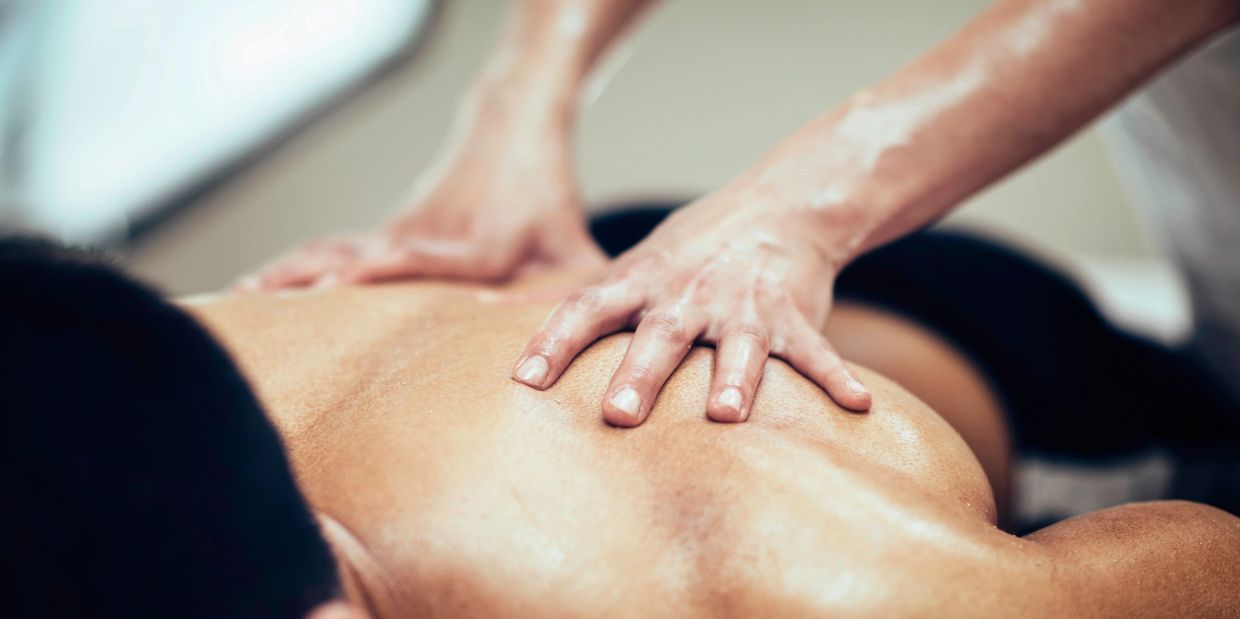 Massage therapy service on the back muscles of a client
