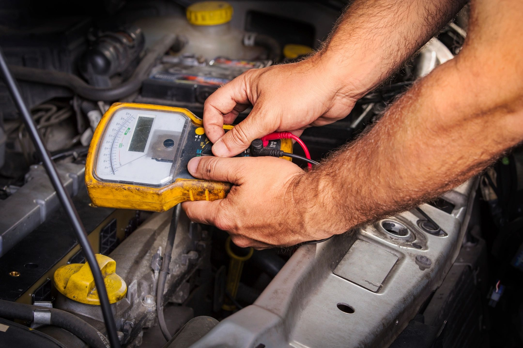 Auto electrician testing battery power