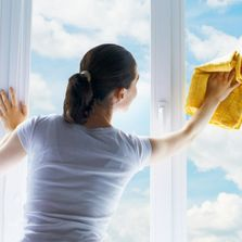 Woman cleaning a window with a yellow cloth
