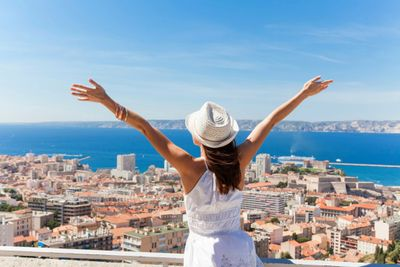 Woman in white summer clothing - feeling healthy - reaching her arms into the air and looking down onto a Mediterranean city - on vacation
