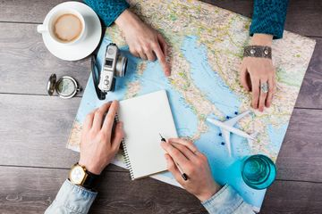 Two adults looking at a map next to a cup of coffee, a compass, a glass of water, and a camera.
